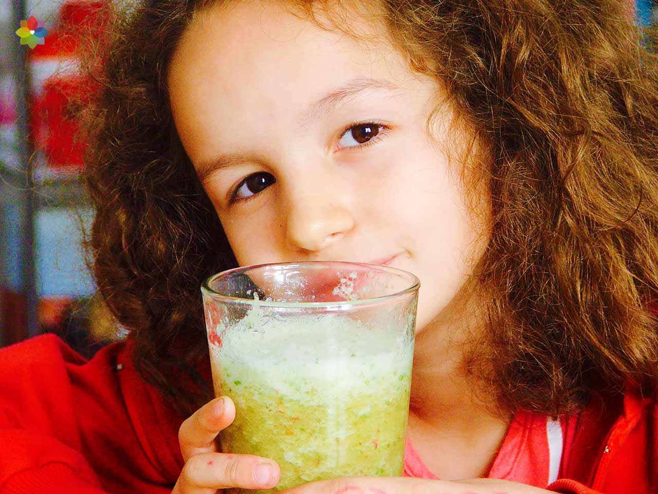 Licuado verde en vaso alto de vidrio, sostenido por una niña
